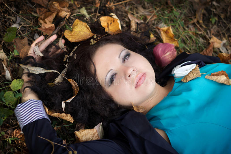 Den härliga flickan ligger på ett gräs royaltyfri bild