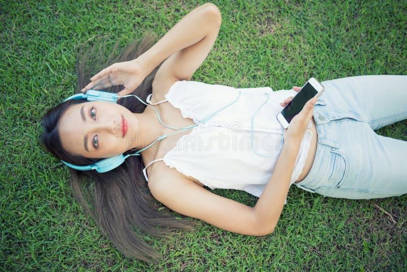 Den härliga flickan lyssnar musik parkerar in royaltyfria bilder