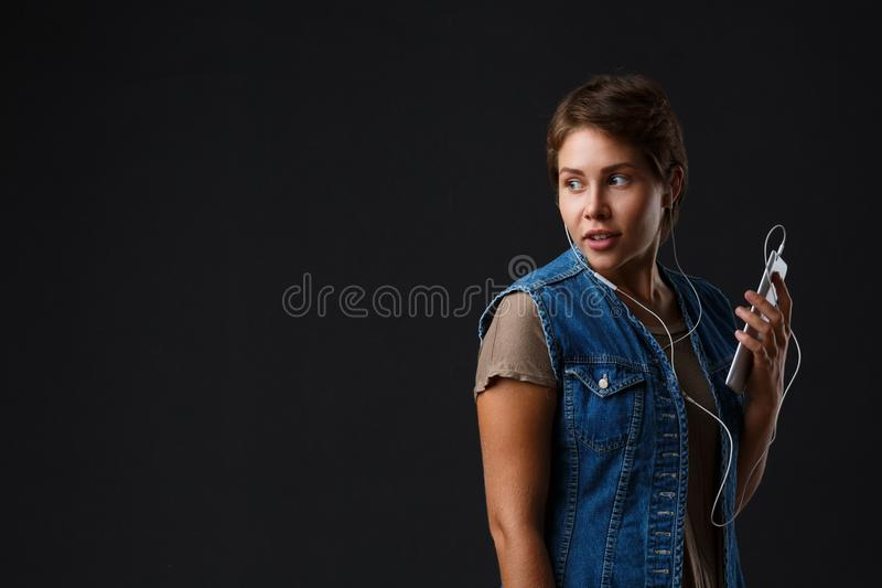 Den härliga flickan lyssnar till musik med hennes telefon på en svart bakgrund royaltyfri foto