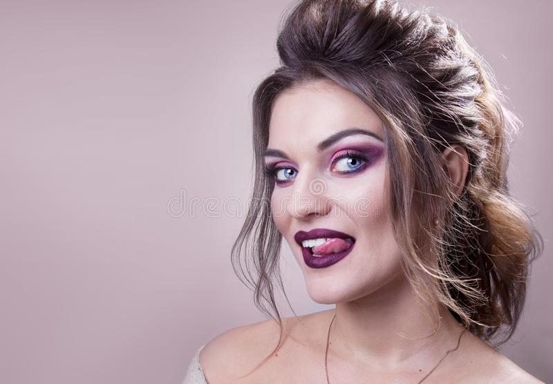 Den härliga flickan med blåa ögon, brun haired härlig sinnesrörelse med tungan på en rosa bakgrund royaltyfri foto