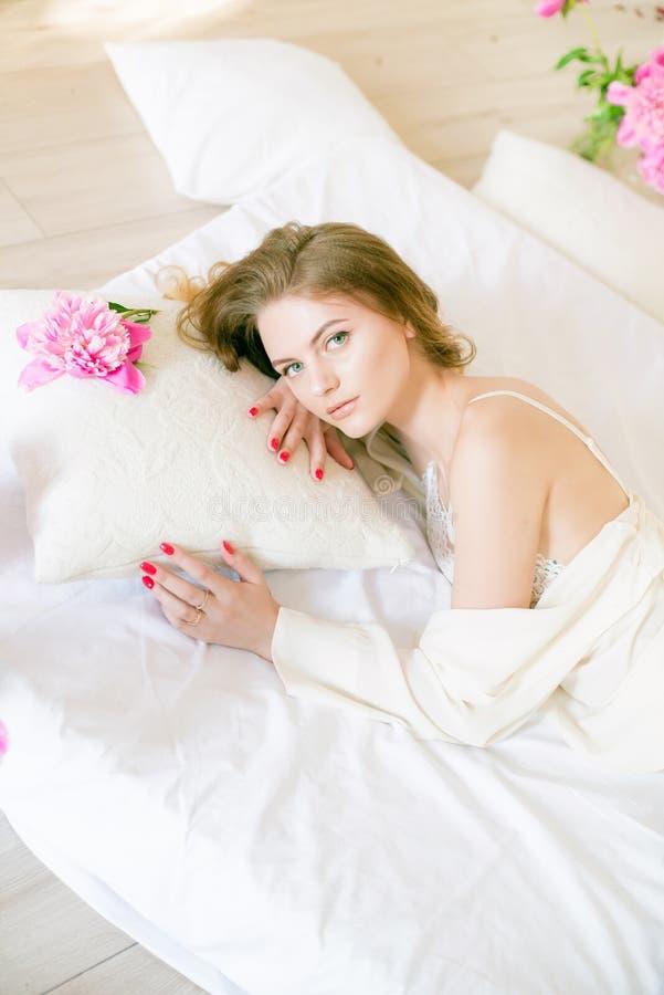 Den härliga flickan med blont hår i vit kläder och underkläderna snör åt med pionblommor royaltyfri bild