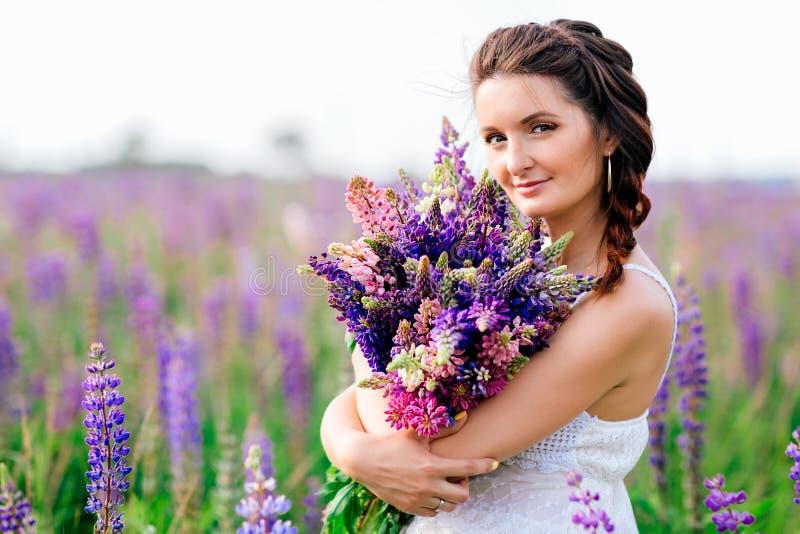 Den härliga flickan med buketten av lupine blommar i händer arkivfoto
