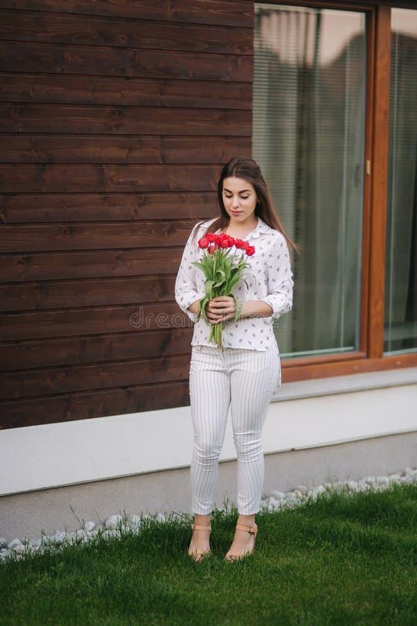 Den härliga flickan med buketten av röda blommor står vid huset spelrum med lampa fotografering för bildbyråer