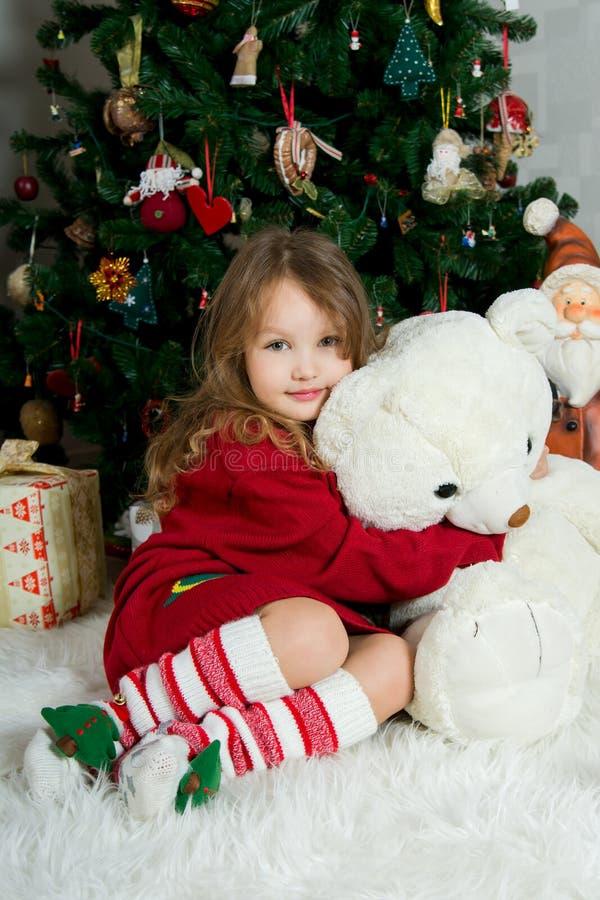 Den härliga flickan med den stora leksaken väntar jul och nytt år royaltyfri fotografi