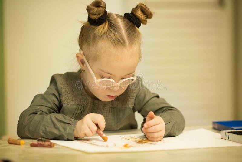 Den härliga flickan med ett Down Syndrome drar med blyertspennor arkivfoto