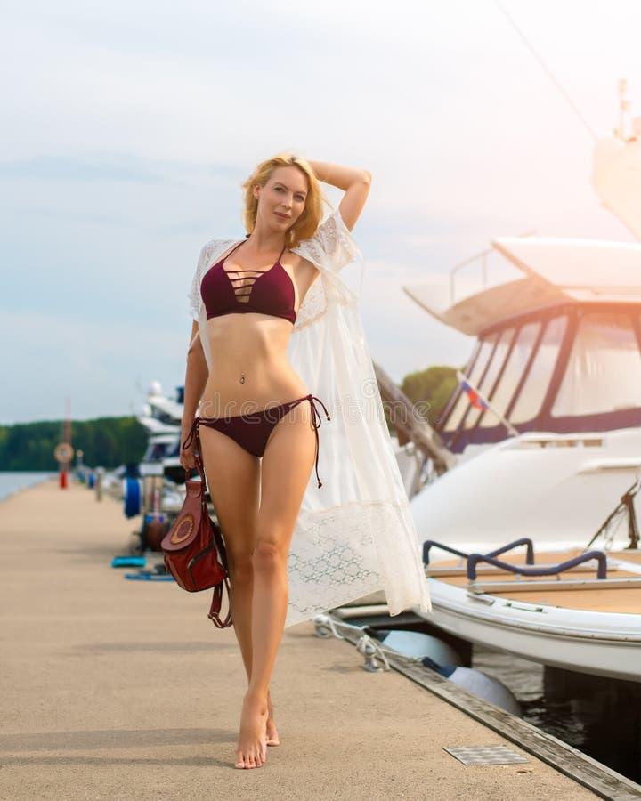 Den härliga flickan med ett slankt diagram står på en träpir i en yachtklubba royaltyfria bilder