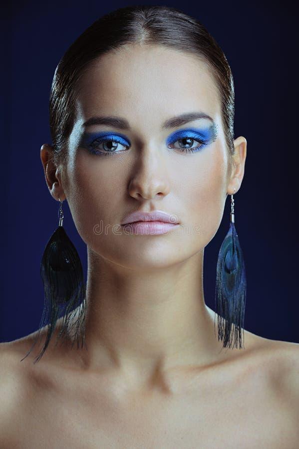 Den härliga flickan med görar perfekt flår i ljust smink för blått i långa örhängen arkivfoton