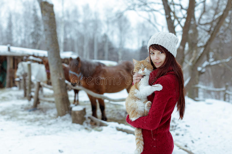 Den härliga flickan med, i det röda tröja- och hattinnehavet och att spela med den lilla fluffiga katten i den snöig vintern, par arkivbild
