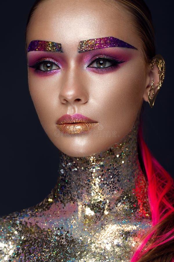 Den härliga flickan med idérikt blänker makeup, mousserar, ovanliga ögonbryn Skönhet är en konstframsida royaltyfria foton