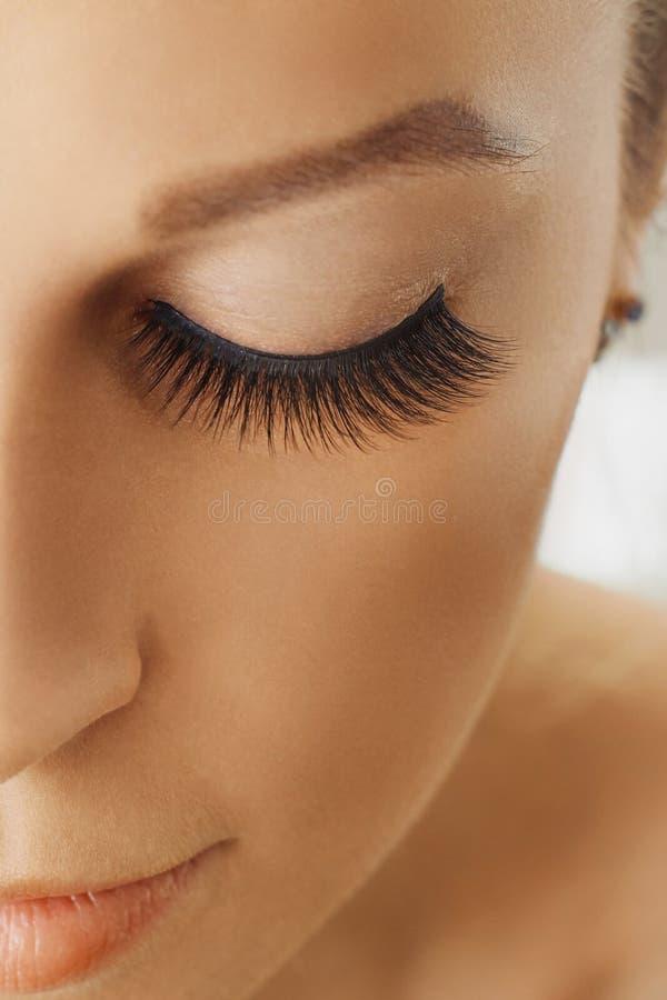 Den härliga flickan med långa falska ögonfrans och gör perfekt hud Ögonfransförlängningar, cosmetology, skönhet och hudomsorg fotografering för bildbyråer