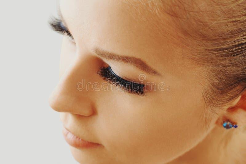 Den härliga flickan med långa falska ögonfrans och gör perfekt hud Ögonfransförlängningar, cosmetology, skönhet och hudomsorg royaltyfri bild