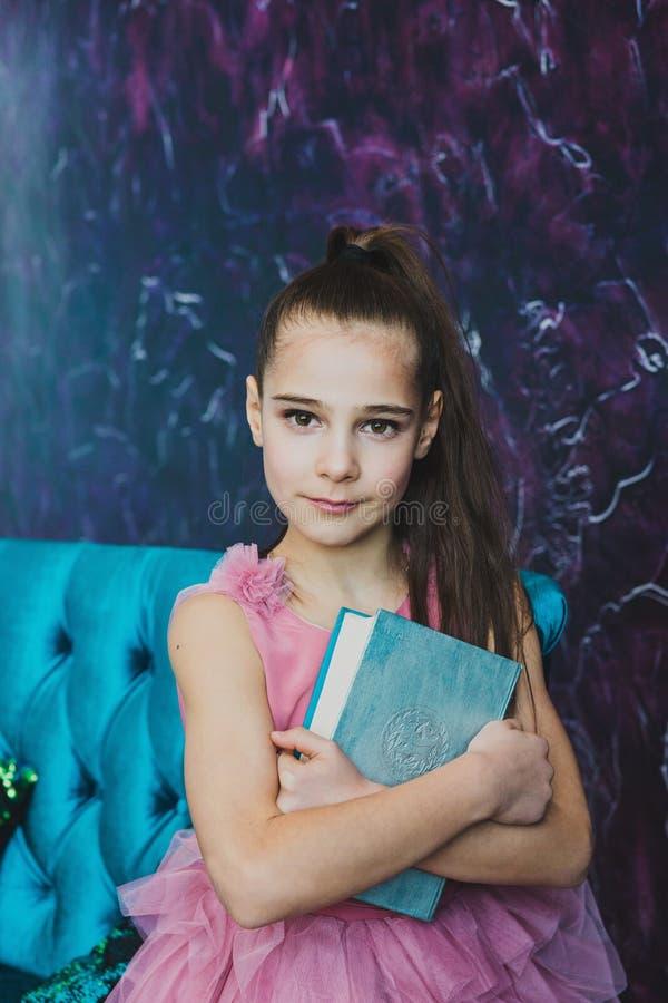 Den härliga flickan med långt brunt hår och den rosa klänningen kramar boken arkivfoton