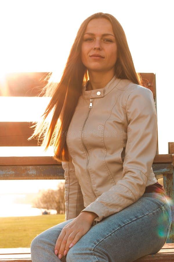 Den härliga flickan med långt hår sitter mitt emot solljuset i ett beigaläderomslag och jeans royaltyfri fotografi