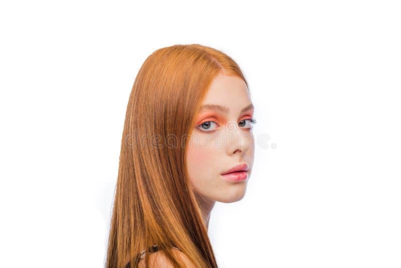 Den härliga flickan med ljust orange smink och kammade långt rött hår på en isolerad bakgrund ser in i ramen arkivfoton