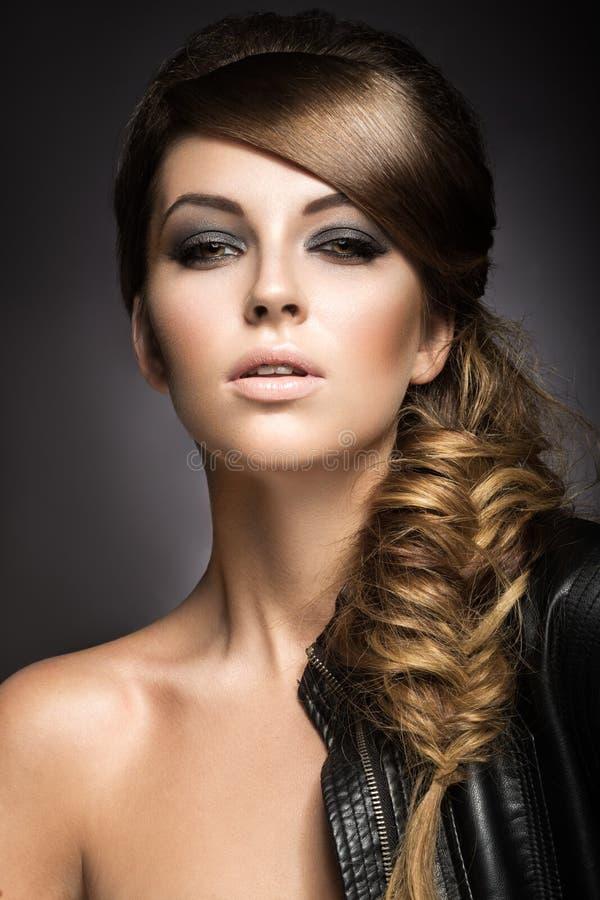 Den härliga flickan med ljust smink, gör perfekt hud och frisyren som en flätad tråd arkivfoton