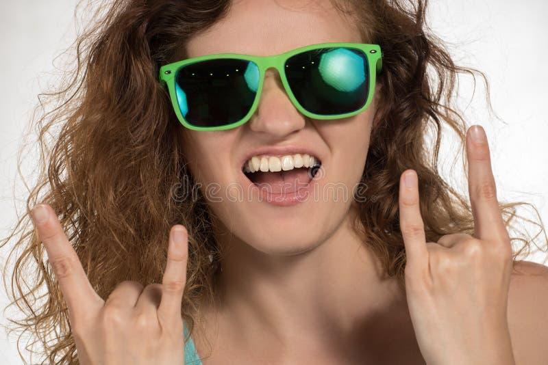 Den härliga flickan med lockigt hår och i solglasögon visar en teckenth royaltyfri fotografi