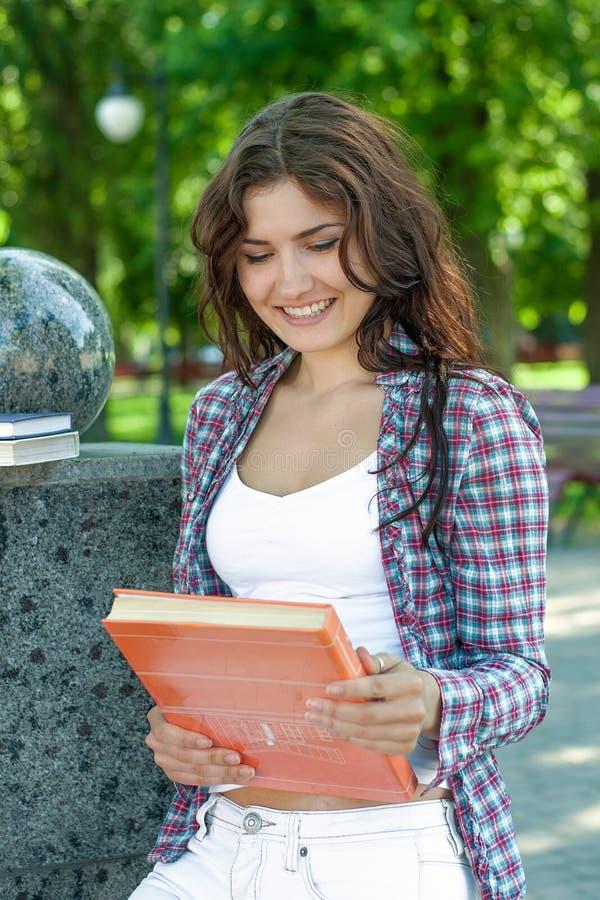 Den härliga flickan med mörkt hår skrattar, genom att se på räkningen av arkivfoto