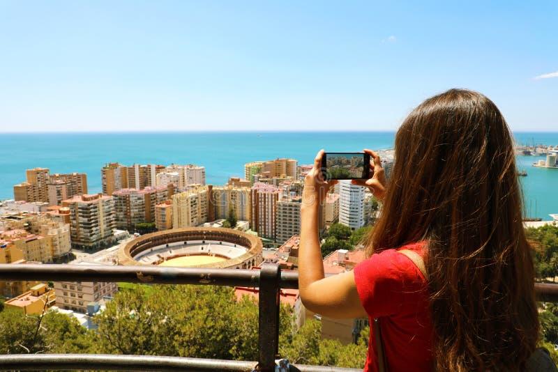 Den härliga flickan med mobiltelefonen tar bilden av det Malaga landskapet med tjurfäktningsarenan, Malaga, Spanien arkivbild