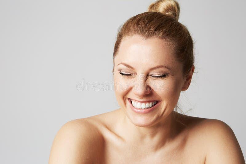 Den härliga flickan med nakna skuldror skrattar med stängda ögon Modellera med det ljusa näcka sminket, grå studiobakgrund royaltyfri fotografi