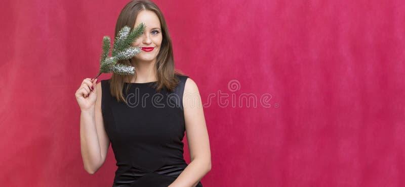 Den härliga flickan med röd läppstift i en svart klänning täcker hennes fac arkivfoton