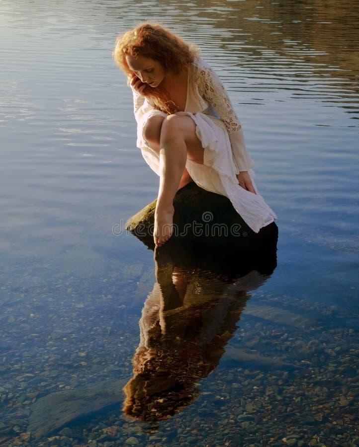 Den härliga flickan med rött hår reflekterade i krusningar och lugnt vatten royaltyfria foton