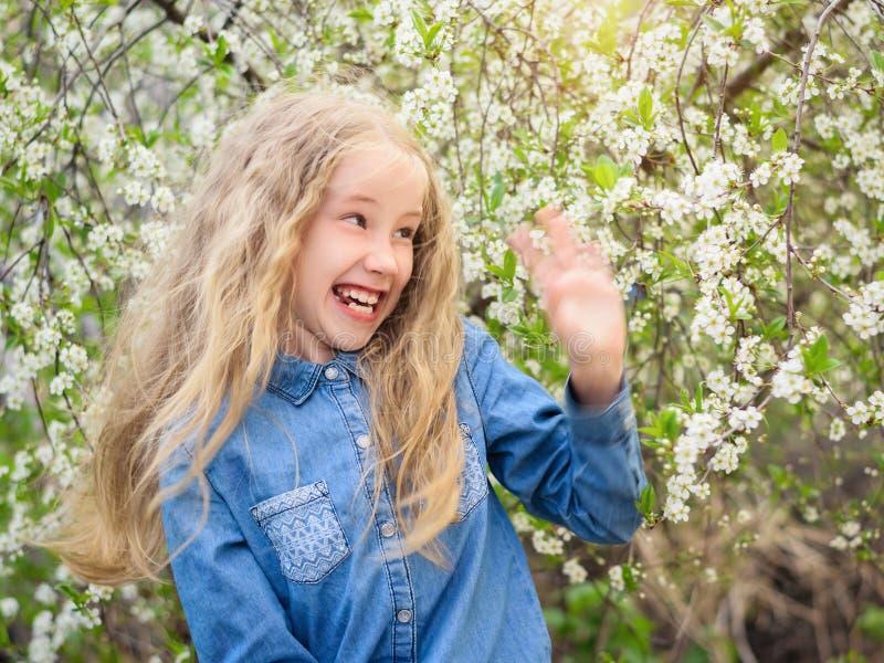 Den härliga flickan med roliga vågor för frodigt hår bort räcker i vårkörsbärträdgård fotografering för bildbyråer