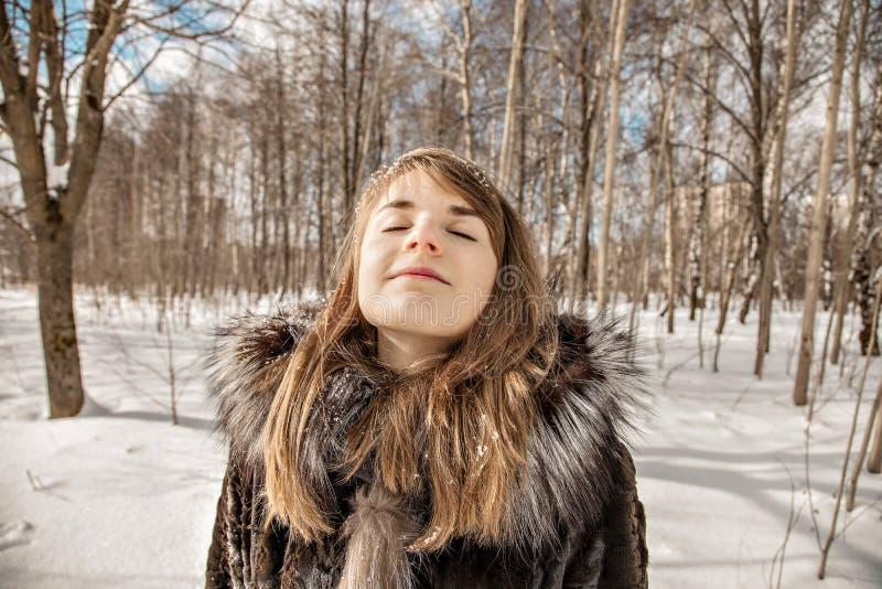 Den härliga flickan med snöflingor i hennes hår tycker om naturen på en solig vinterdag royaltyfria foton