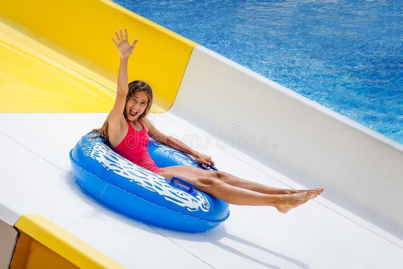 Den härliga flickan på den uppblåsbara cirkeln som rider vattenglidbanan med handen upp i aqua, parkerar royaltyfria bilder
