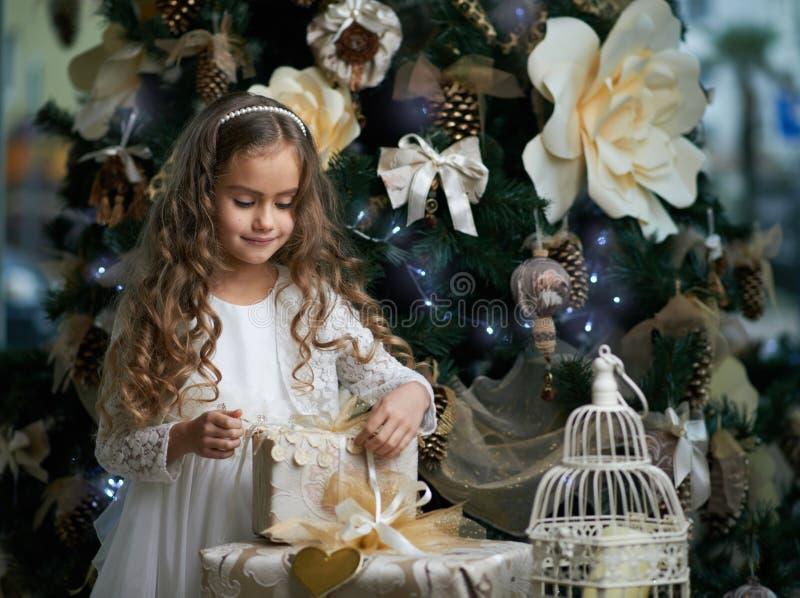 Den härliga flickan packar upp gåvor royaltyfria foton