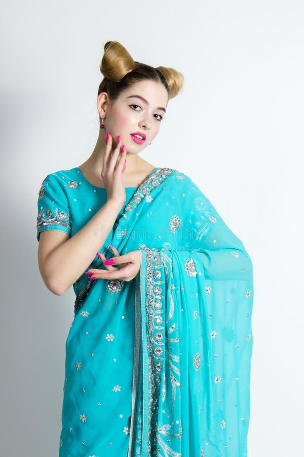 Den härliga flickan poserar i blå sari Ser som en docka och en indierkvinna royaltyfria bilder