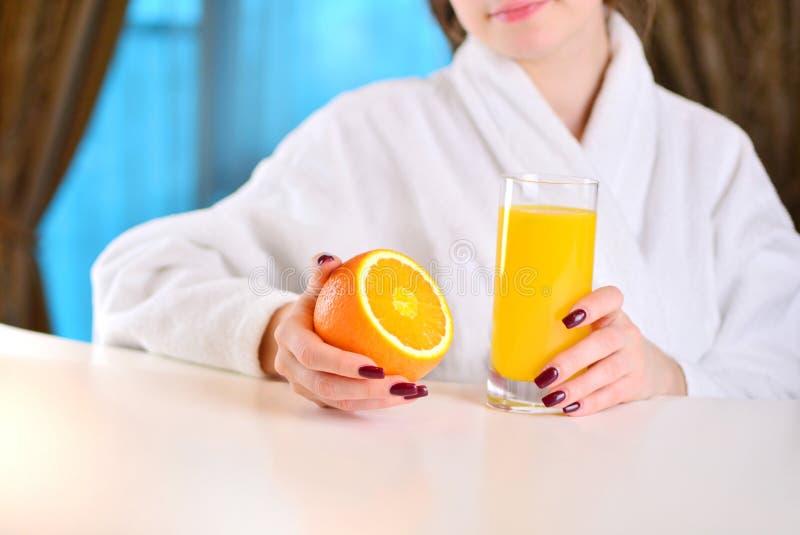 Den härliga flickan rymmer en apelsin med nytt royaltyfri foto