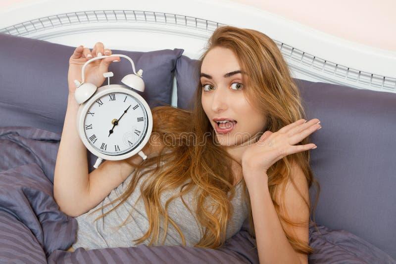 Den härliga flickan rymmer en klocka och lögner i sängsovrum Emotionell härlig kvinna som ligger i säng på hennes fridag royaltyfri fotografi