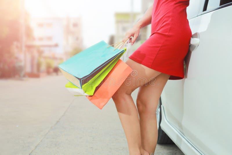 Den h?rliga flickan rymmer shoppingp?sar bredvid bilen royaltyfria bilder