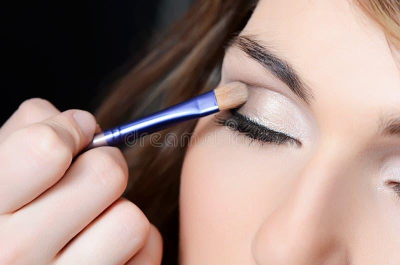 Den härliga flickan satte makeupen på framsidan arkivfoton