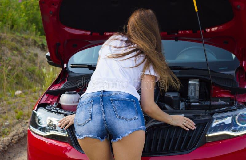 Den härliga flickan ser motorn under huven av bilen royaltyfri fotografi
