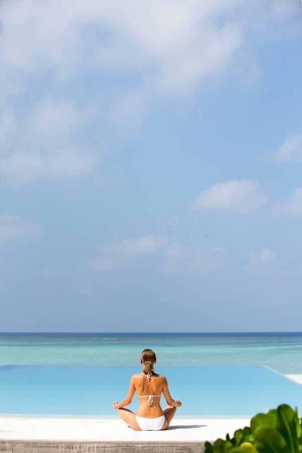 Den härliga flickan sitter i en posera av en lotusblomma och mediterar på kusten Maldiverna arkivfoton