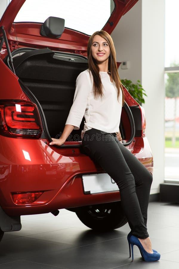 Den härliga flickan sitter på bilstammen fotografering för bildbyråer