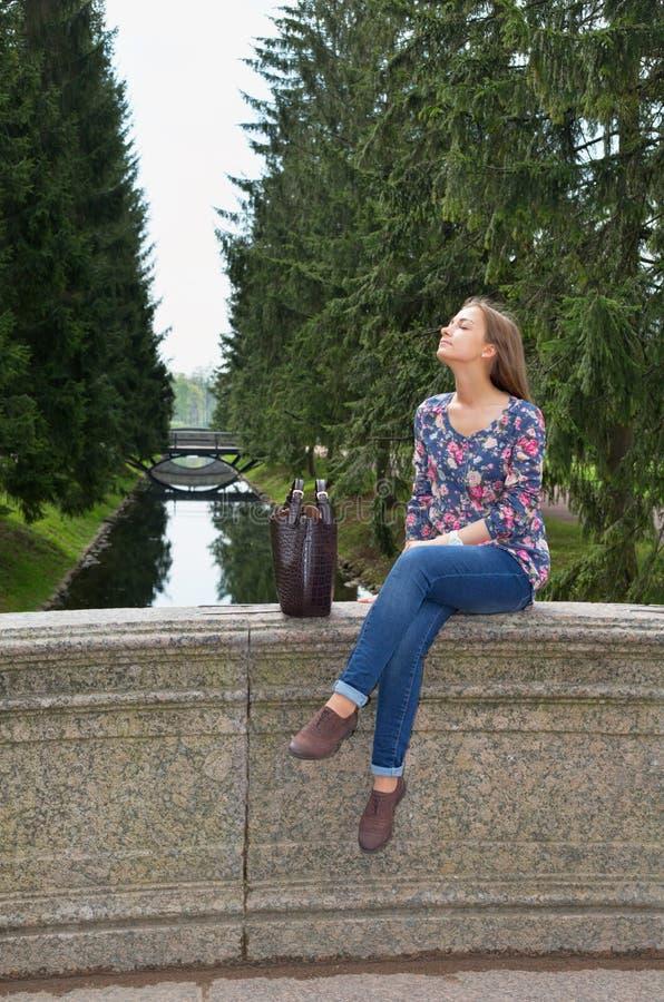 Den härliga flickan sitter på en gammal stenbro arkivbilder