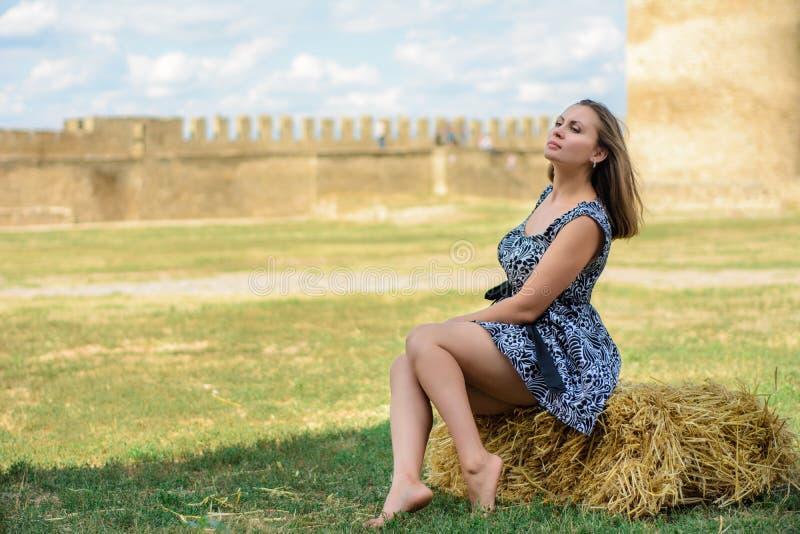 Den härliga flickan sitter på ett sugrör mot en bakgrund av en fästning arkivbild