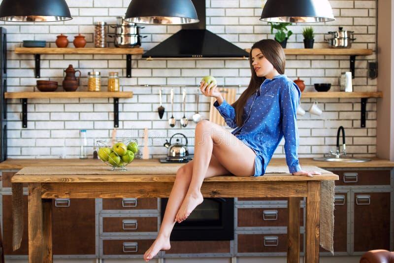 Den härliga flickan sitter på köksbordet med det gröna äpplet i blå pyjamas Energin av morgonen, magin av kvinnlig skönhet, arkivfoto