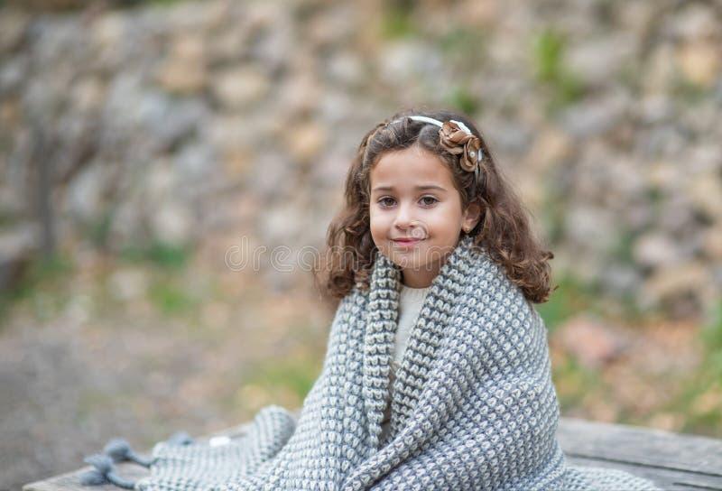 Den härliga flickan sitter på naturen och värme sig med en varm stucken filt arkivfoto
