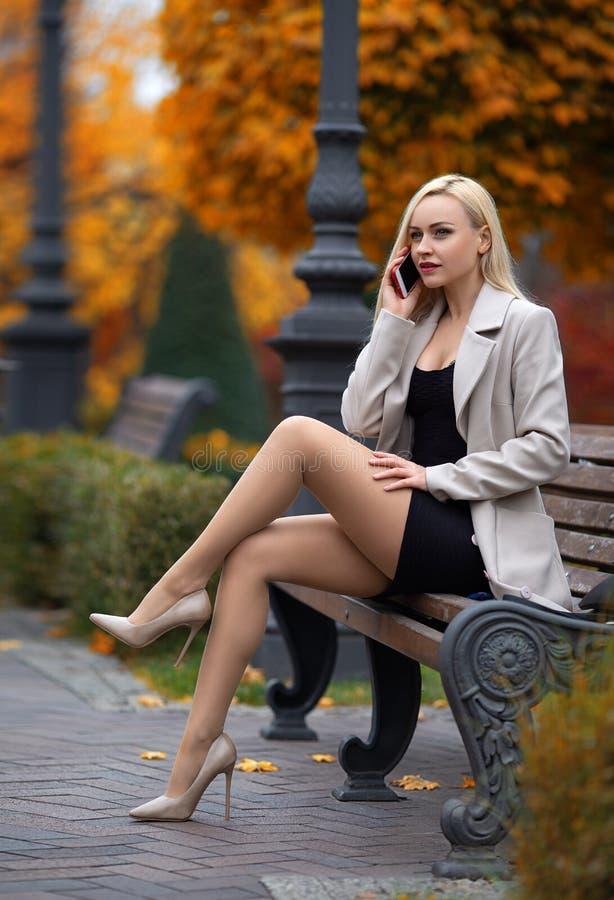 Den härliga flickan som kallar via mobiltelefonen i, parkerar royaltyfria bilder