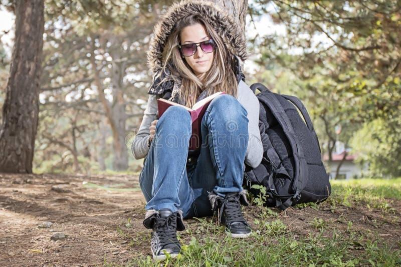 Den härliga flickan som läser en bok i höst, parkerar royaltyfri fotografi