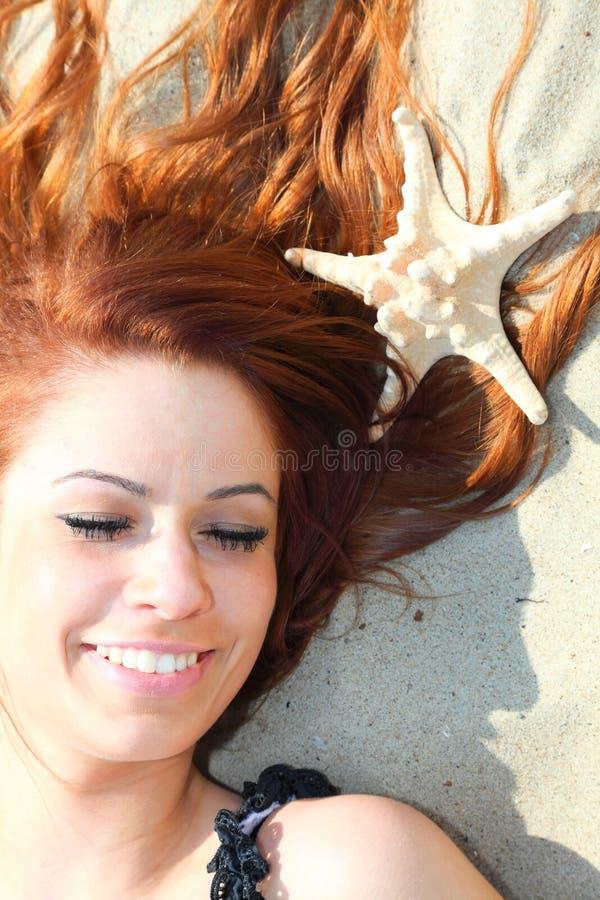 Den härliga flickan som lies på havet seglar utmed kusten med, beskjuter natursemester royaltyfri bild