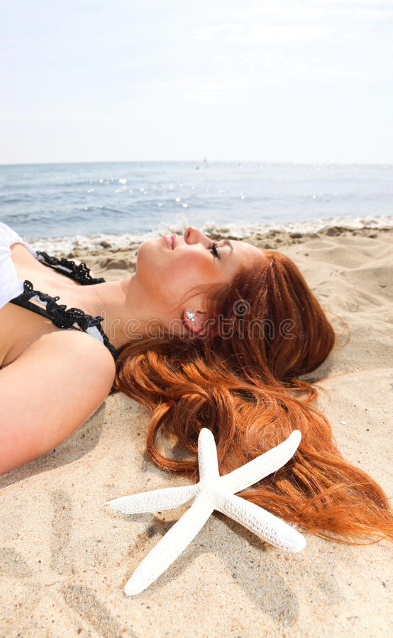 Den härliga flickan som lies på havet seglar utmed kusten med, beskjuter natursemester royaltyfri foto