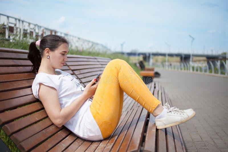 Den härliga flickan som sitter på bänk i, parkerar med telefonen i händer royaltyfria bilder