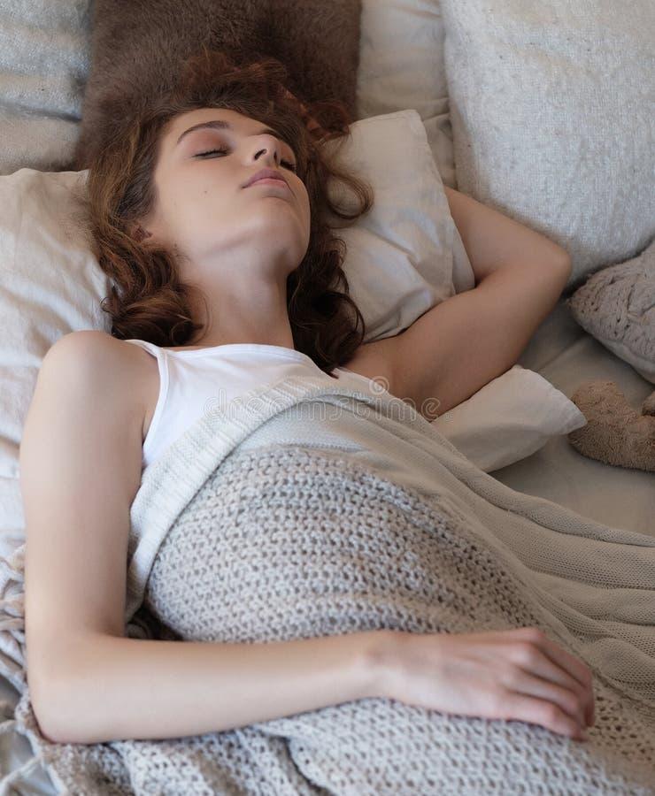 Den härliga flickan sover i sovrummet som ligger på säng arkivfoton