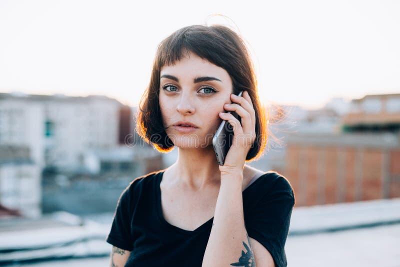 Den härliga flickan talar på telefonen i solnedgång arkivfoton
