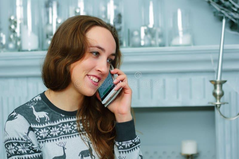 Den härliga flickan talar till mobiltelefonen under chrismas-att ge sig eller tagna berömmar arkivfoton