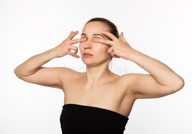 Den härliga flickan utför anti--att åldras övningar framsidakondition för anti-nedsutten hud royaltyfria foton